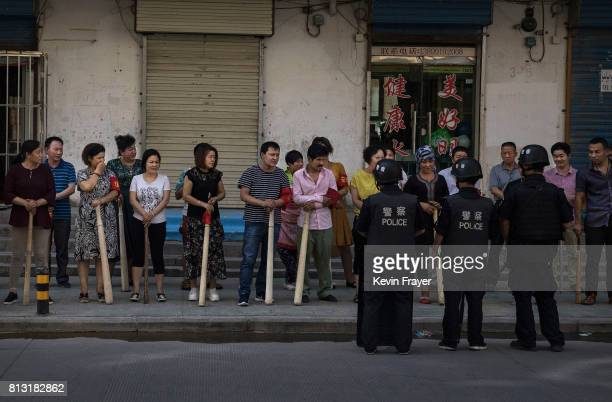 A mix of ethnic Uyghur and Han shopkeepers hold large wooden sticks as they are trained in security measures on June 27 2017 next to the old town of...