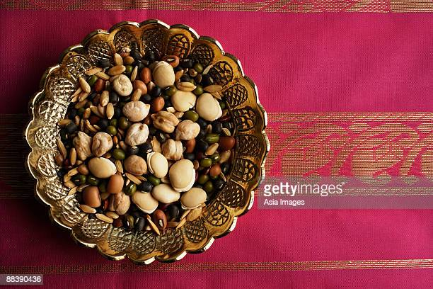 Mix of Indian beans, seeds and nuts in brass dish on pink sari cloth
