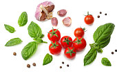 mix of slice of tomato, basil leaf, garlic and spices isolated on white background. top view