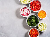 Mix of vegetable bowls for salad or snacks on gray background. Diet detox concept