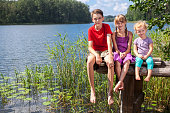Three children of different age - teenager boy, elementary age girl and toddler girl sitting on a wooden pier by a forest lake looking at camera smiling