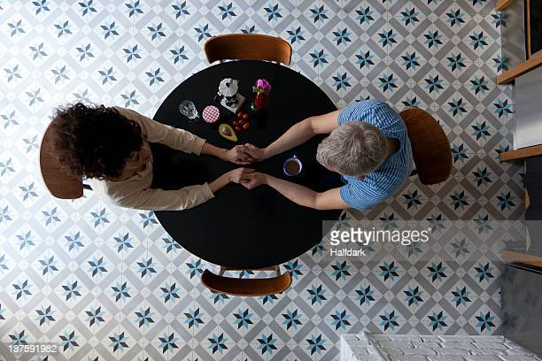 A mixed age couple holding hands at the breakfast table, directly above