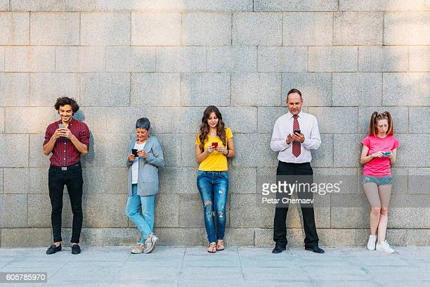 Mixed age range og people texting in a row