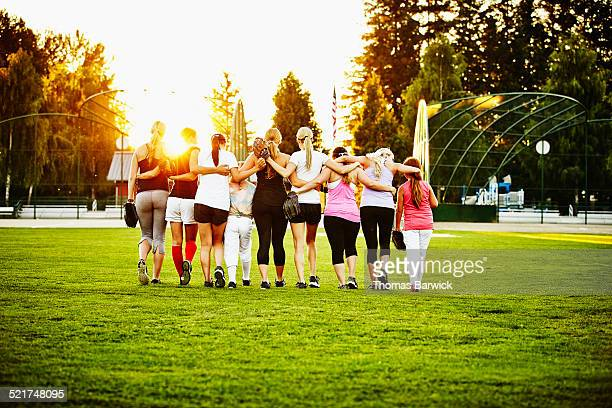 Mixed age softball players walking together