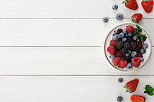 Assorted garden and wild berries background. Mix of fresh organic strawberries, raspberries, blueberries and blackberries in glass bowl on white wooden table, top view, copy space