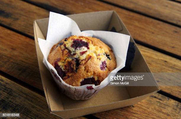 Mixed berry, white chocolate and coconut muffin in waxed paper in a cardboard tray on a wooden outdoor table