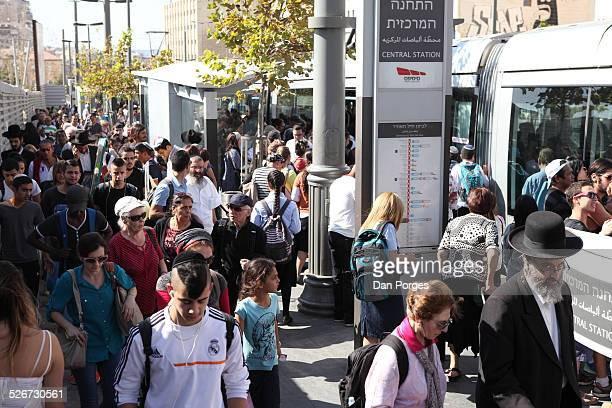 A mixed crowd of people men and women Orthodox and secular Jews and Arabs just got off others board the Light Train or Light Rail at the Central Bus...