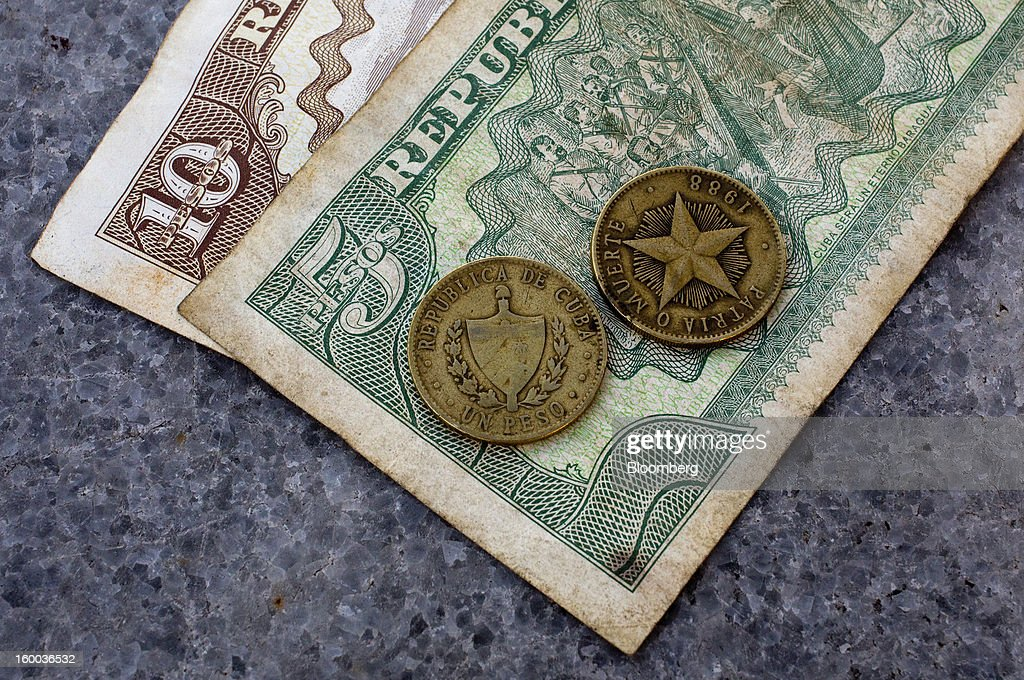 Mixed denomination non-convertible peso, or 'chavito,' notes and coins, one of two official currencies in Cuba, are seen in this arranged photograph in Havana, Cuba, on Thursday, Jan. 17. 2013. In a country where the average monthly salary is $19, according to Cuba's statistics agency, even buying an airplane ticket will be beyond the reach of most of the island's 11 million residents as President Raul Castro begins easing travel rules on the communist island. Photographer: Andrey Rudakov/Bloomberg via Getty Images