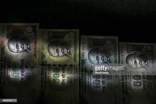 Mixed denominations of Indian rupee banknotes are arranged for a photograph in Mumbai India on Thursday Apr 16 2015 India's rupee has appreciated 12...