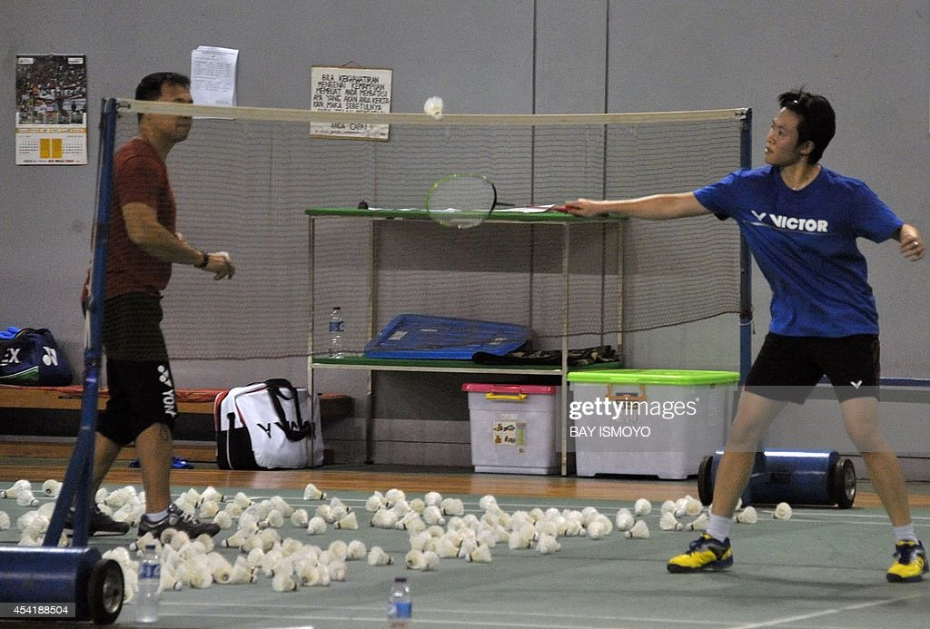 Mixed doubles badminton player Liliyana Natsir (R) of Indonesia practices with his coach Richard Mainaky (L) in Jakarta on August 26, 2014 in preparation for the 17th Asian Games in Incheon from September 19 to October 4. Indonesia is targeting their medal hopes in badminton in the top Asian sporting event. AFP PHOTO / Bay ISMOYO