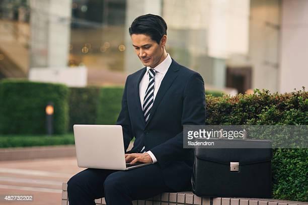 Gemischte Abstammung Geschäftsmann Arbeiten auf der compiuter außerhalb