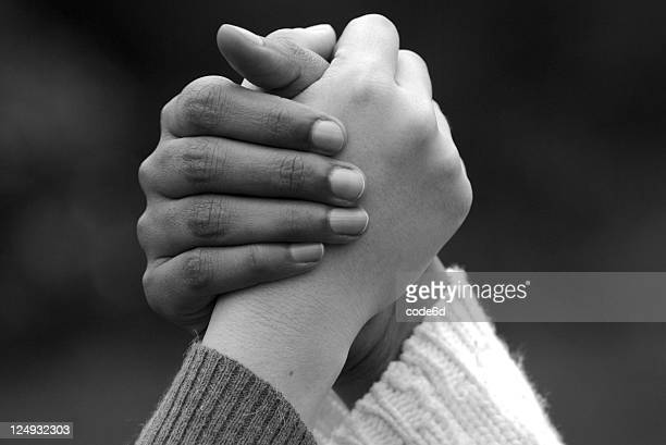 Mixed ethnicity women holding hands, teamwork concept, black and white