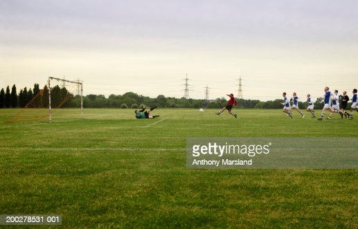 Mixed football match, opposing team chasing player towards goal : Stock Photo