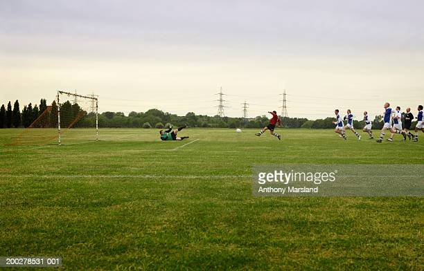 Mixed football match, opposing team chasing player towards goal