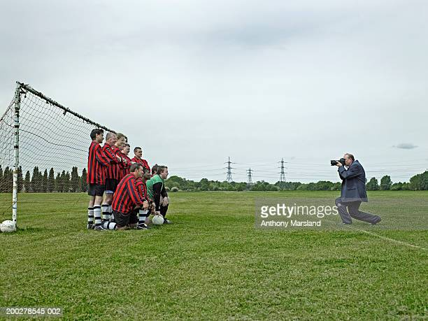 Mixed football team being photographed in front of goal, side view