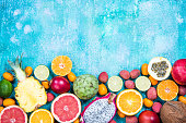 Mixed fresh vibrant exotic fruits, border background. Top view,copy space.