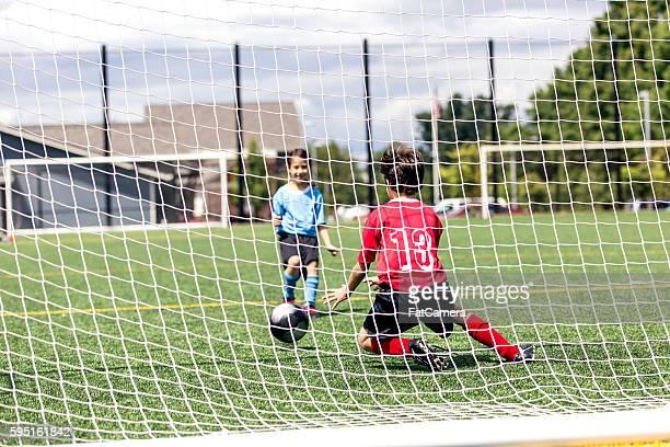 Mixed gender soccer team makes a goal attempt