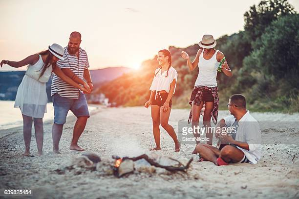 Mixed group of friends dancing together at a beachparty