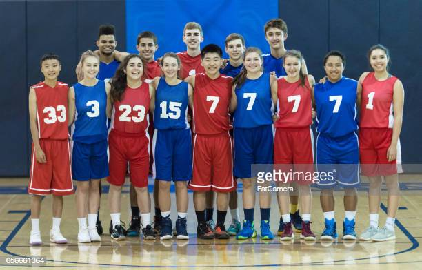 Mixed group of high school basketball players posing for team photograph