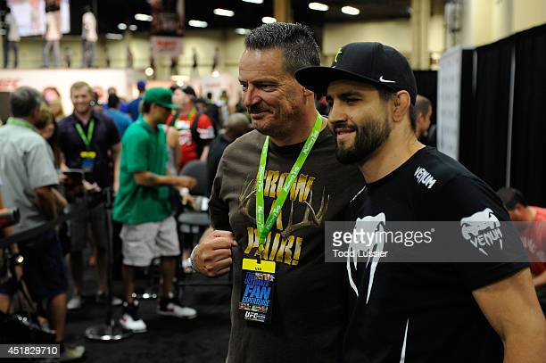 Mixed martial artist Carlos Condit poses with a fan during the UFC Fan Expo 2014 during UFC International Fight Week at the Mandalay Bay Convention...