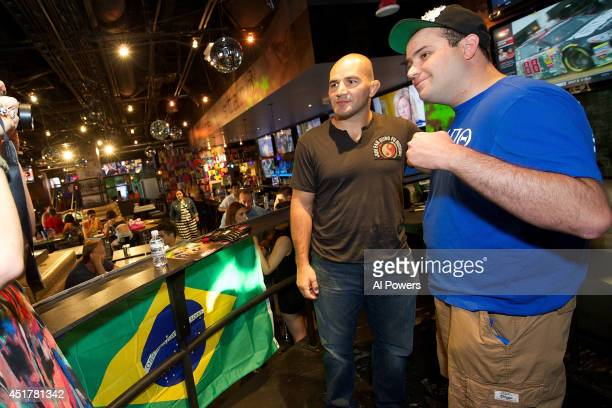 Mixed martial artist Glover Texeira poses with a fan at the UFC Brazilian party during UFC International Fight Week inside the Rockhouse at The...