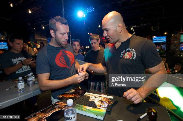 Mixed martial artist Glover Texeira signs an autograph for a fan at the UFC Brazilian party during UFC International Fight Week inside the Rockhouse...