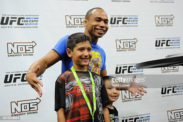 Mixed martial artist John Dodson poses with fans during the UFC Fan Expo 2014 during UFC International Fight Week at the Mandalay Bay Convention...