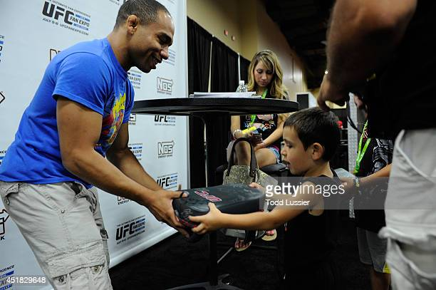Mixed martial artist John Dodson signs autographs for fans during the UFC Fan Expo 2014 during UFC International Fight Week at the Mandalay Bay...