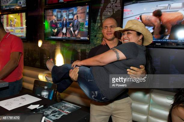 Mixed martial artist Junior Dos Santos interacts with a fan at the UFC Brazilian party during UFC International Fight Week inside the Rockhouse at...