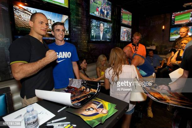 Mixed martial artist Junior Dos Santos poses with a fan at the UFC Brazilian party during UFC International Fight Week inside the Rockhouse at The...