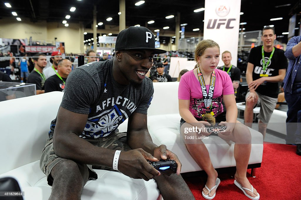 Mixed martial artist Phil Davis plays the new EA UFC video game with fans during the UFC Fan Expo 2014 during UFC International Fight Week at the...