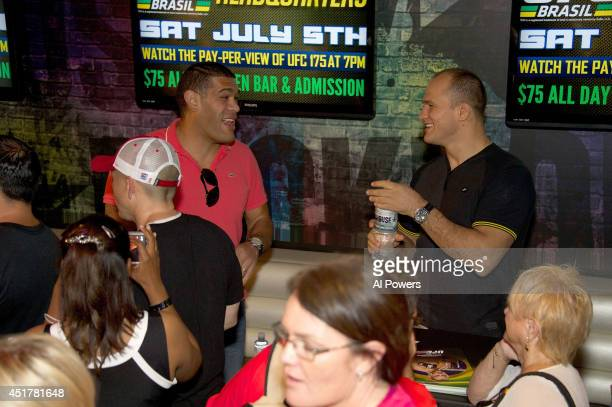 Mixed martial artists Antonio 'Bigfoot' Silva and Junior Dos Santos interact at the UFC Brazilian party during UFC International Fight Week inside...