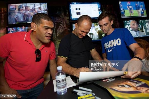 Mixed martial artists Antonio 'Bigfoot' Silva and Junior Dos Santos sign autographs for a fan at the UFC Brazilian party during UFC International...