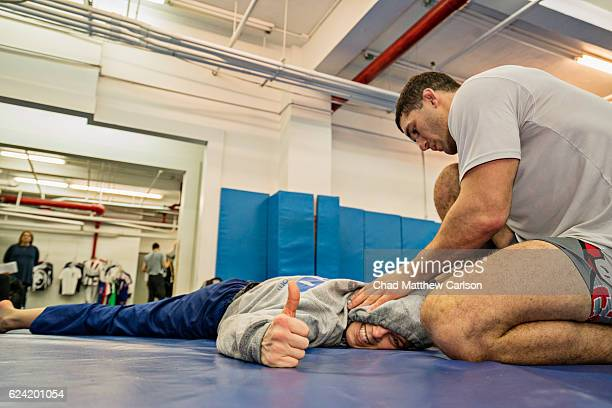 UFC 205 Preview Katlyn Chookagian stretching during working out with Kyle Cerminara during training session photo shoot at Renzo Gracie Academy New...