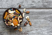 mixed nuts and dried fruits in a bowl over rustic wooden table. top view with copy space. healthy food
