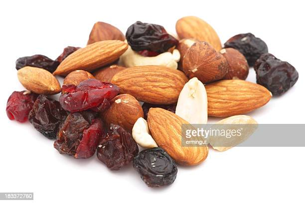 Mixed nuts and dry fruits pile isolated on white
