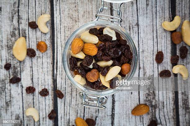 Mixed nuts and raisins in glass on wood