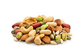 Macro shot of mixed nuts arranged in a heap isolated on white background. Nuts included in the composition are pistachios, hazelnut, pine nut, almonds, pumpkin seeds, macadamia nuts, sunflower seeds,