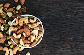 """Healthy food and snack : mixed nuts in white ceramic bowl from above,  Walnut, pistachios, almonds, hazelnuts and cashews.""""n""""n"""