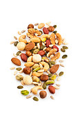 Vertical shot of mixed nuts arranged in a heap isolated on white background. Nuts included in the composition are pistachios, hazelnut, pine nut, almonds, pumpkin seeds, macadamia nuts, sunflower seed