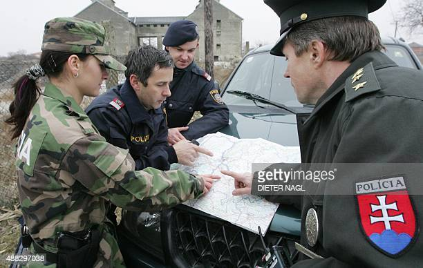 A mixed police unit from Austria and Slovakia examines a map 19 December 2007 in Jarovce near Bratislava days before Slovakia becomes a member of the...