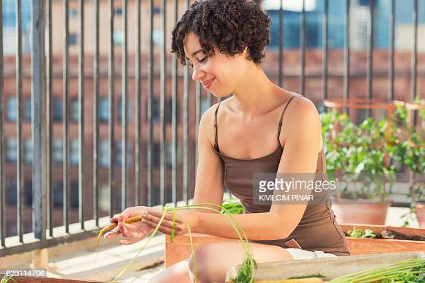 Mixed race American woman roof gardening