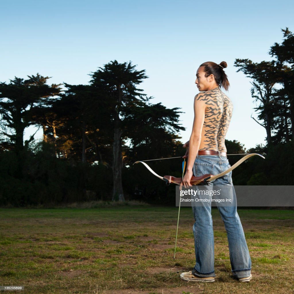 Mixed race archer holding bow and arrow : Stock Photo