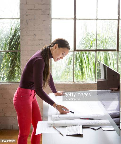 Mixed race architect examining blueprints in office