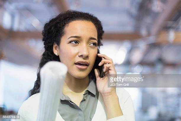 Mixed race architect talking on cell phone