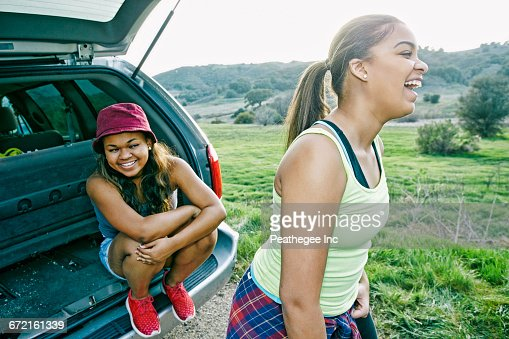Mixed Race at hatch of car laughing