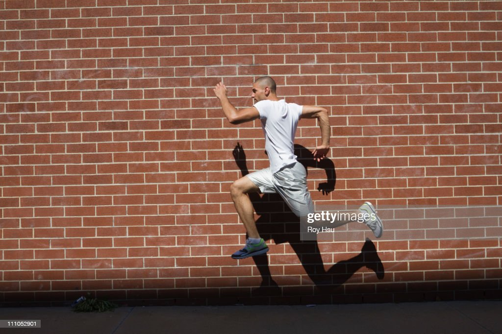 Mixed race athlete running in urban area : Stock Photo
