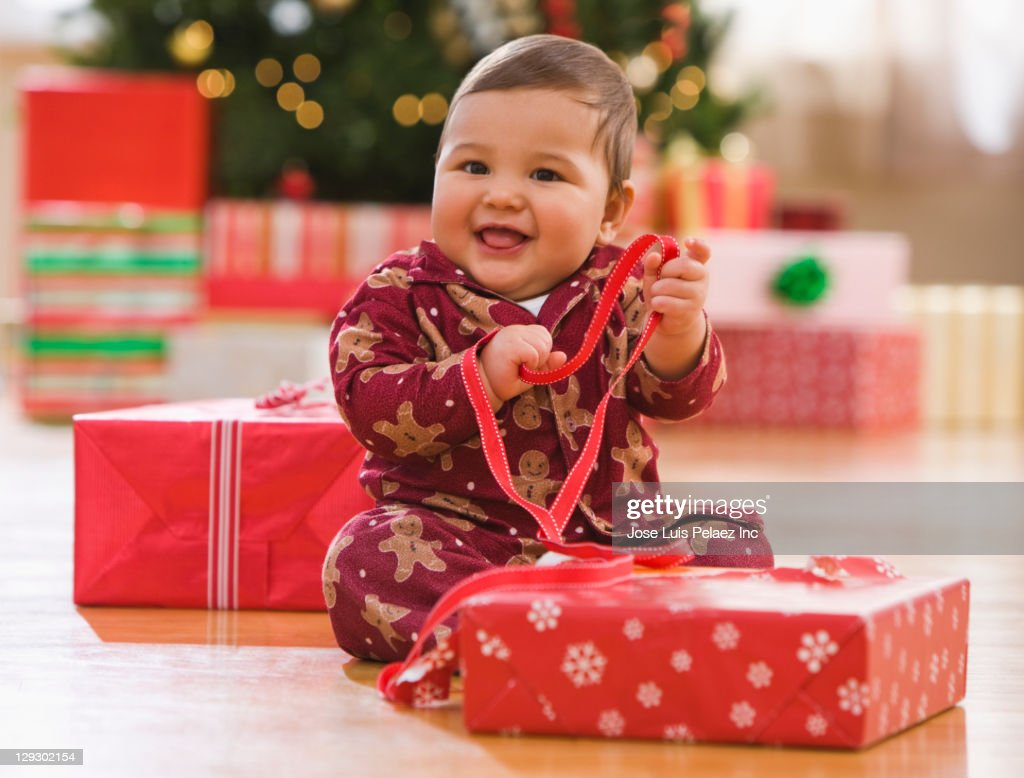 Mixed race baby boy opening Christmas gift : Photo
