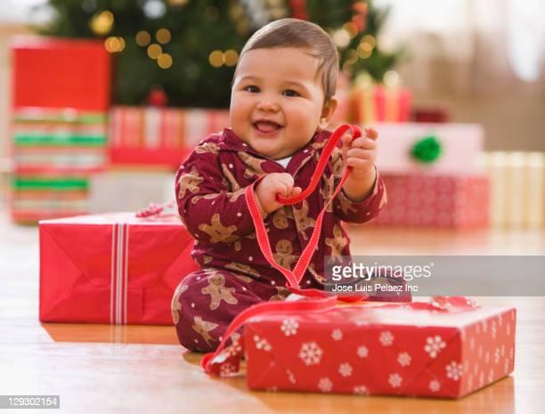 Mixed race baby boy opening Christmas gift
