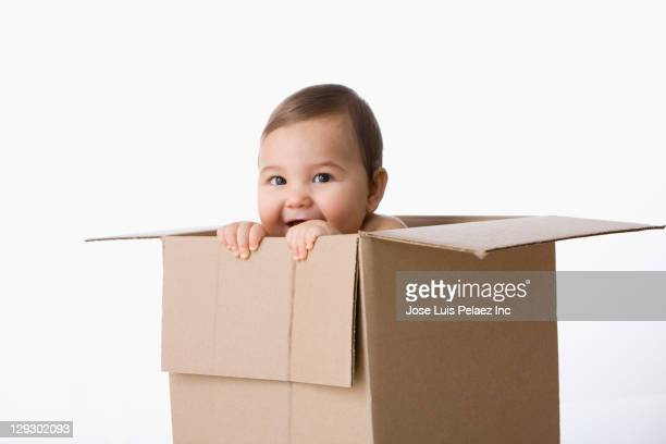 Mixed race baby boy playing in cardboard box